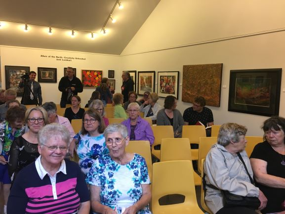 Guests sit in the art gallery as they wait for the questiona and answer session to begin