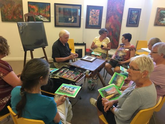 Students sit around Jack Lockhart holding onto their paintings