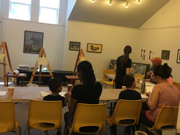 Families work together to create a painting in the art gallery